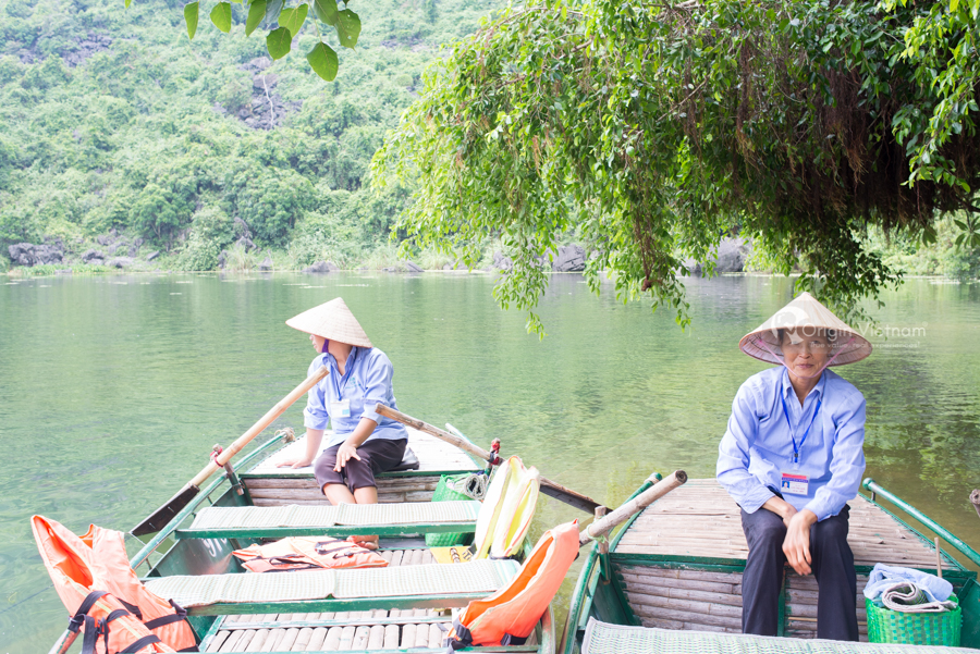Woman rowing boat wait visitor visiting Trinh Temple